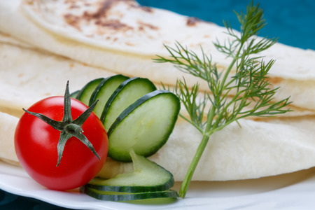 Fresh vegetables with a tortilla bread, close up, selective focus on the tomato