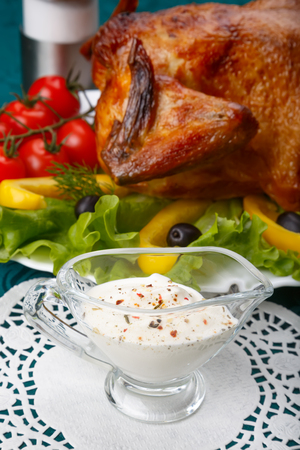 White garlic sauce in front of whole roasted chicken served with fresh vegetables, selective focus on sauce