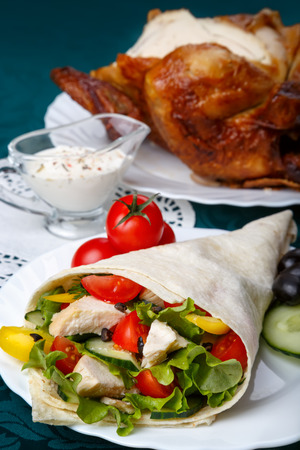 Shawarma on a white plate with a white sauce, doner kebab, traditional roll with meat and pita bread, selective focus on the filling Stock Photo