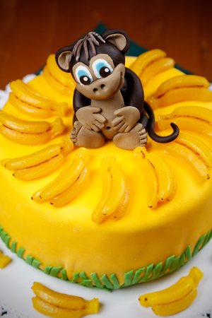 Cake witn funny monkey among marmalad bananas on the top for the Chinese New Year 2016