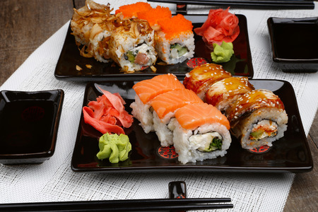 Sushi set on plate with wasabi and marinated ginger on wooden table with soy sauce Stock Photo