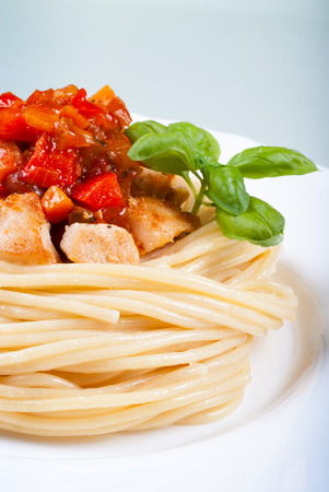 Pasta spaghetti, chicken, sweet and sour sauce topping with basil on white plate Stock Photo