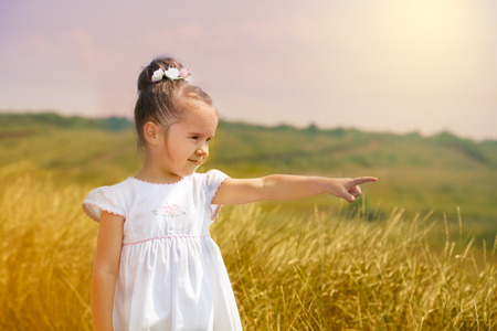 Cute little girl in the white dress in a field pointing by a finger at the right side