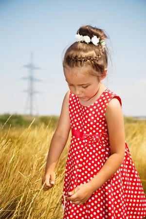 Cute little girl in the red dress in a field