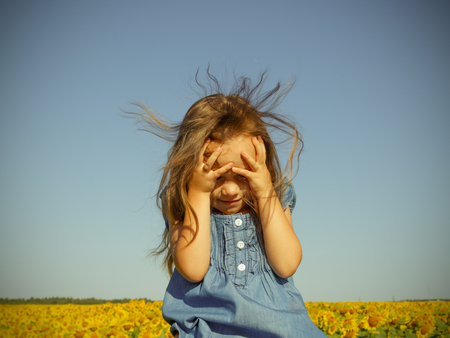 Little girl in blue dress over a field of sunflowers is hiding her face by hands. Sunny summer day.