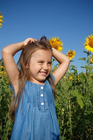 Little girl in blue dress in a field of sunflowers.Sunny summer day.