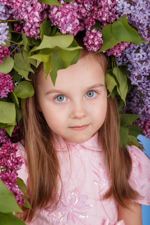 Beautiful girl with the lilac spring wreath on the head as a flowers hair style