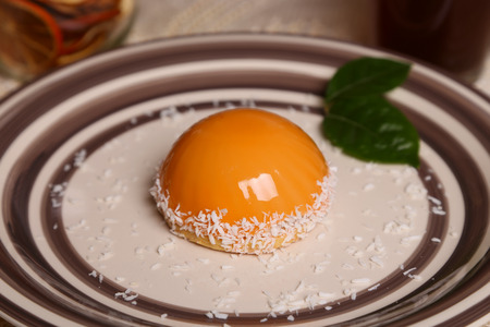 Mousse dessert decorated with yellow mirror glaze