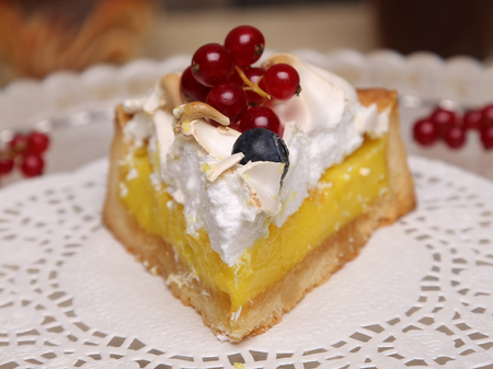 Piece of lemon tart with a meringue and red currant berries