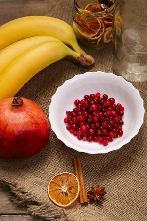 Cranberry, pomegranate and banana. Healthy food, vitamins. Rustic background. Healthy eating, dieting. Different fruits and berries on old wooden table.