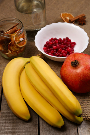 Bananas, cranberry and pomegranate. Healthy food, vitamins. Rustic background. Healthy eating, dieting. Different fruits and berries on old wooden table.