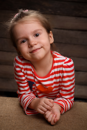 Cute beautiful happy little girl in front of rural wooden background and looking into the camera