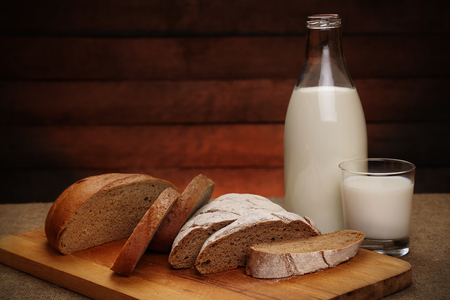 Milk and bread. Milk in a glass bottle and rye bread on a rustic wooden background. Bio products for the breakfast. Healthy food. Stock Photo