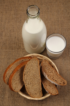 Milk and bread. Milk in a glass bottle and rye bread on a sackcloth background. Bio products for the breakfast. Healthy food. Top view.