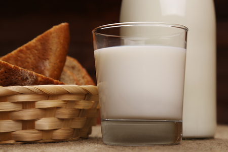 Milk and bread. Milk in a glass bottle and rye bread on a dark background. Bio products for the breakfast. Healthy food. Close up.