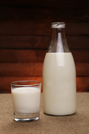 Milk in a drink glass and in a glass bottle on a rustic wooden background. Bio and organic products.