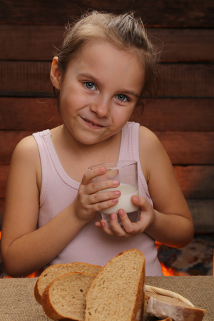 Cute little smiling girl is holding a glass of milk. Morning in a countryside home. Simple breakfast. Milk and bread. Healthy lifestyle. Stock Photo