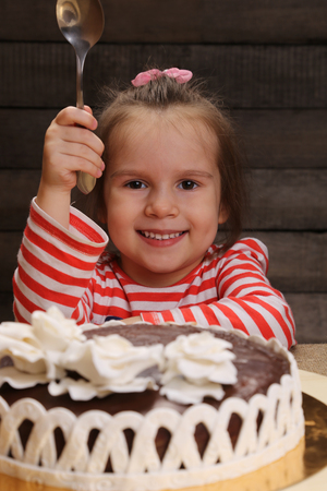joys: Cute excited smiling little girl with spoon in hand going to eat chocolate cake. The joys of childhood. Celebration party.