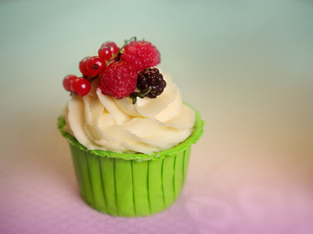 Cupcake with cream cheese frosting decorated with raspberry and redcurrant on top over colorful background. Sweet dessert. Shallow DOF. Selective focus on the raspberry.