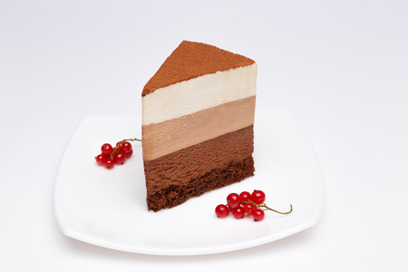slice of the three chocolate mousse cake on a white plate