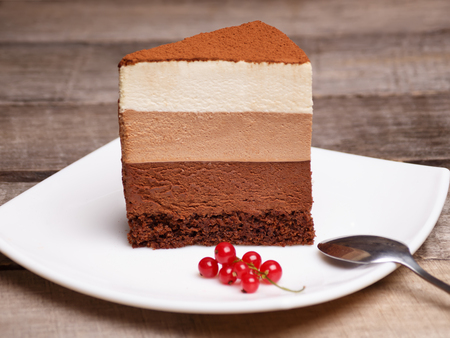 slice of the three chocolate mousse cake on a white plate against a wooden background Stock Photo