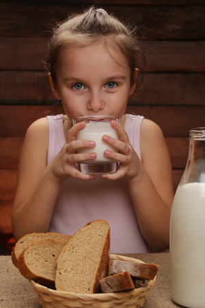 Cute little girl is drinking milk. Morning in a countryside home. Simple breakfast. Milk and bread. Healthy lifestyle.