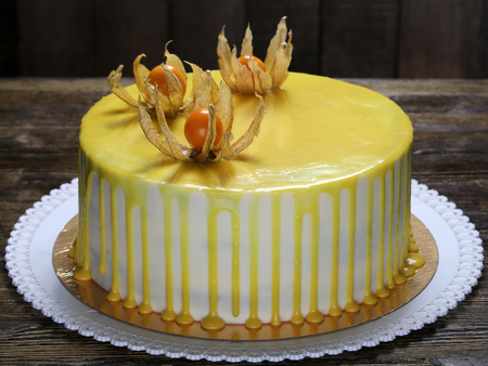 classic carrot cake decorated with a yellow glaze and physalis berries on the top