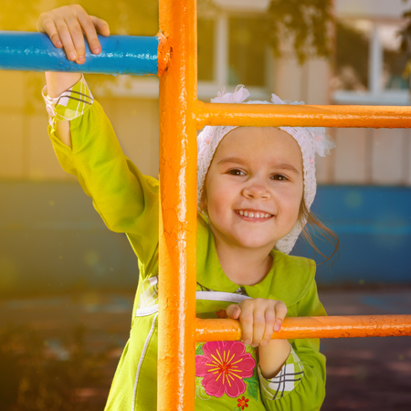 Happy little girl playing on a playground