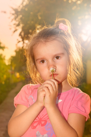 Little girl with flower in sunset rays of sun, warm colored background Stock Photo