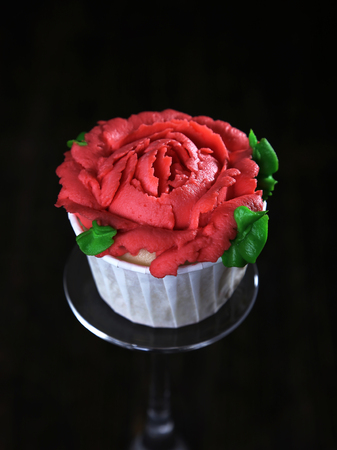Cupcake with red cream frosting on top as rose flower decoration on black background Stock Photo