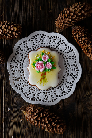 homemade gingerbread cookie with the handmade icing flowers decoration on a wooden table Stock Photo