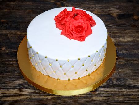 white fondant cake with red cream sugar flowers