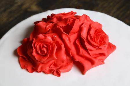 red cream sugar flowers on a white fondant cake