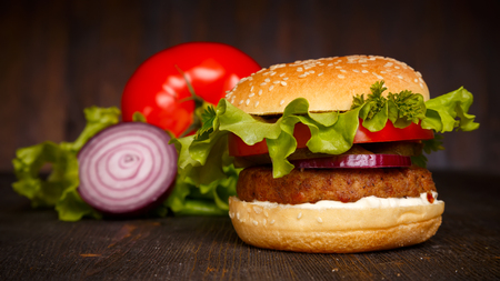 big fresh tasty burger with vegetables on a dark wooden table, hamburger, fast food Stock Photo