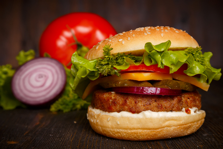 big fresh tasty burger with vegetables on a dark wooden table, cheeseburger, fast food