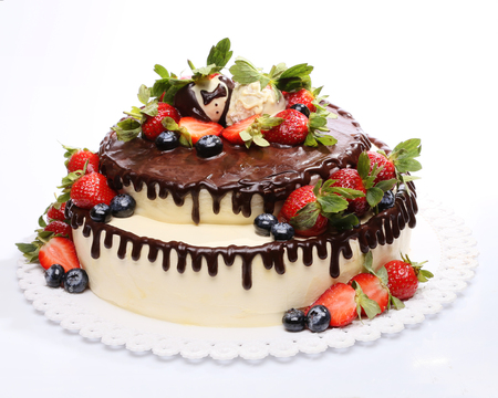 Chocolate mousse cake decorated with strawberries and blueberries on a white background Stock Photo