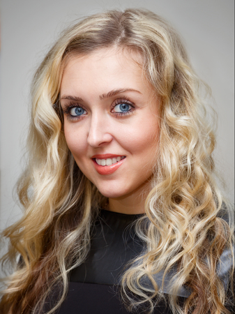 Portrait of a smiling young charming woman with long wavy blonde hair over a gray background Stock Photo