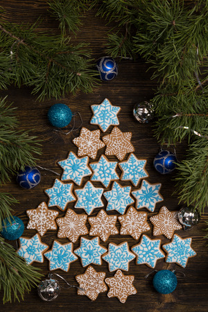 Christmas gingerbread snowflake cookies decorated with icing on wooden table, flatlay. Christmas and New Year traditions, winter holidays, homemade sweets, festive food
