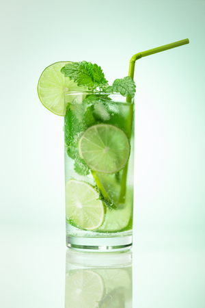Mojito cocktail with sliced lime fruit and mint. Traditional summer cold drink. Banco de Imagens