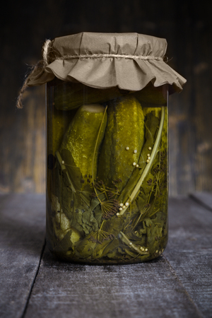 Pickled cucumbers in a glass jar on rustic countryside wooden background