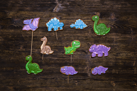 Homemade gingerbread cookies with the handmade icing decoration as funny dinosaurs. Wooden surface. Gift for kids.