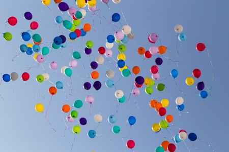 A lot of colorful balloons flying away in clear blue sky Banco de Imagens