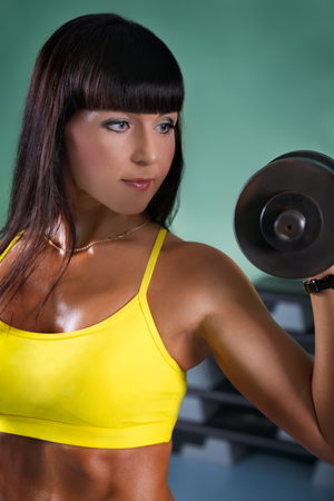 Fitness girl workout with dumbbell in gym room. Modern female lifestyle concept.