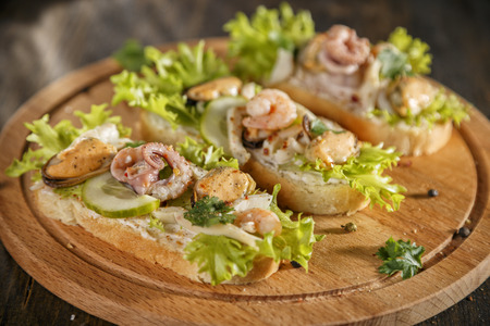 Seafood bruschetta toasted bread topped with fresh salad, parsley, cucumber, creme cheese, shrimp, octopus, mussel Banco de Imagens