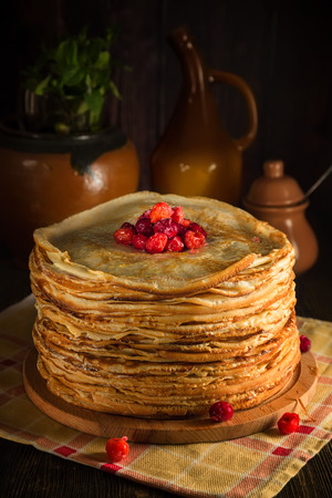 The pile of crepes pancakes with sugared cowberry on top