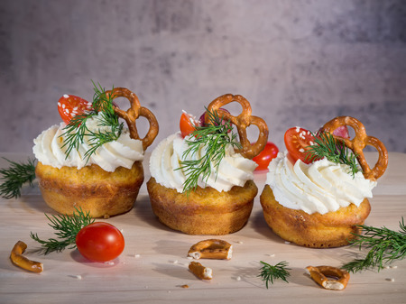 Homemade unsweetened savory appetizer cupcakes with cream cheese, tomato and little salted pretzel snack