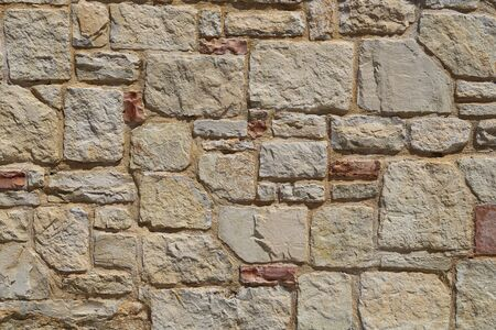 Texture of a stone wall.  House stone wall with square tiles texture background. Part of a stone fence, for background or texture