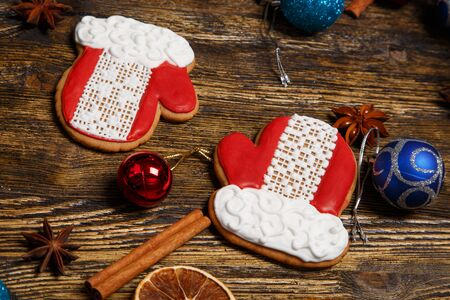 Christmas mittens gingerbread cookies decorated with icing on wooden table, flatlay. Christmas and New Year traditions, winter holidays, homemade sweets, festive food Banco de Imagens