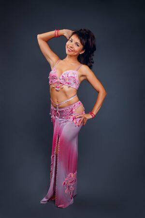 Bauchtänzerin, die Bauchtanz im ethnischen rosa Kostüm zum Tanzen auf grauem Hintergrund durchführt