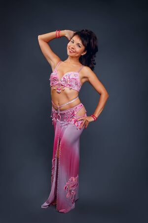 Danzatrice del ventre che esegue la danza del ventre nel costume rosa etnico per ballare su sfondo grigio
